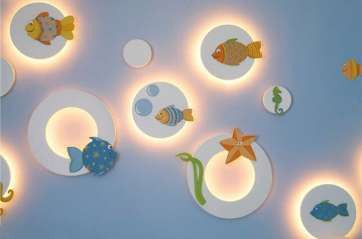 Como decorar un muro de la habitacion del bebe con originales lamparas traslucidas, formando diseño acuatico haciendo las figuras marinas, con madera y pintura al agua.