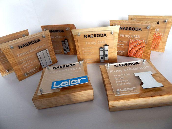 Statuetki nagrody dla firm wykonane z połączenia kilku materiałów: drewna – podstawa pleksi satynowej – grawerowana tablica pleksi czarnej – napis nagroda laminatu grawerskiego – elementy graficzne, logo