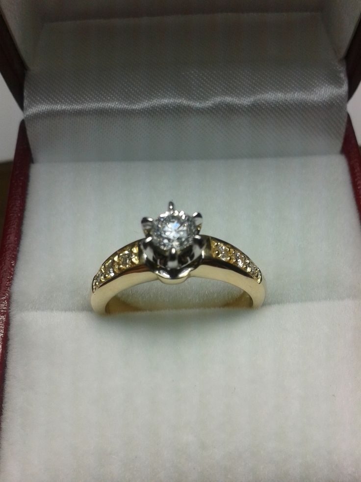 Anillo de compromiso, fabricado con oro amarillo y oro blanco, engastado con diamante central en chatón de 6 uñas, y diamantes laterales engastados al grano.