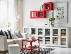 White living room with two-seater sofa and low storage combined with open and closed storage.  Here with red coffee table on wheels and red wall cabinet with glass doors.