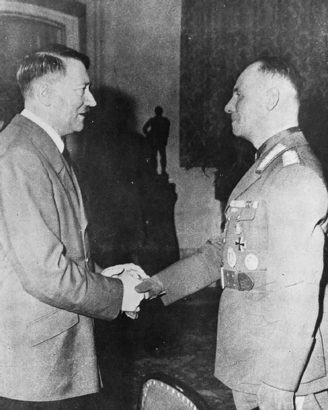 Field Marshal Erwin Rommel shakes hands with Adolf Hitler upon the former's return from Africa in 1943. The atmosphere is obviously somber because Rommel's return signified the effective cessation of Germany's presence in Africa.