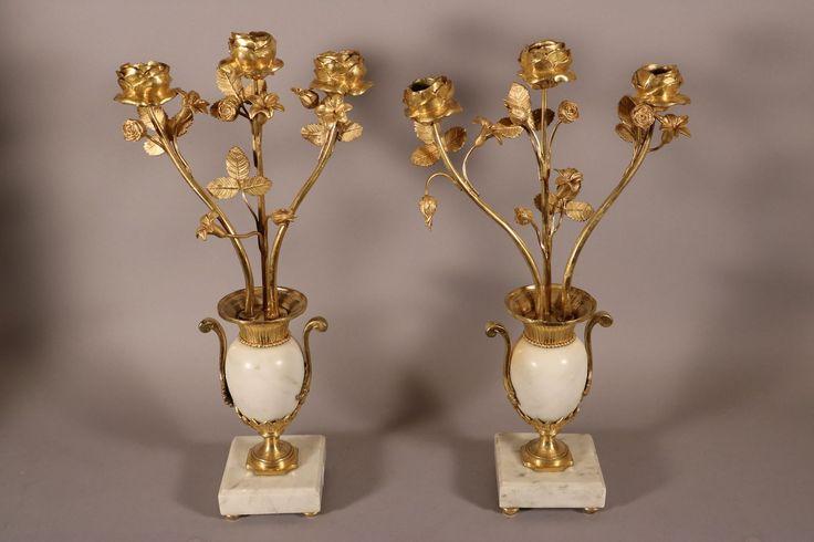 Brochure Paire de candélabres, bronze doré, marbre blanc, époque Louis XVI. Paire de candélabres en bronze doré et marbre blanc à trois branches de roses au naturel. Les trois roses les plus développées servent de binet. Chaque branche comporte trois ou quatre fleurs plus ou moins écloses. Les trois bras de lumière émergent d'un vase …