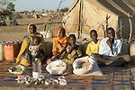 (MODEL RELEASED IMAGE). The Aboubakar family of Darfur province, Sudan, in front of their tent in the Breidjing Refugee Camp, in eastern Chad, with a week's worth of food. D'jimia Ishakh Souleymane, 40, holds her daughter Hawa, 2; the other children are (left to right) Acha, 12, Mariam, 5, Youssouf, 8, and Abdel Kerim, 16. Cooking method: wood fire. Food preservation: natural drying. Favorite food: D'jimia: soup with fresh sheep meat. The Aboubakar family is one of the thirty families…