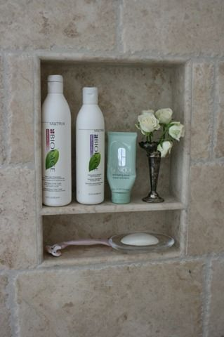 A custom niche with shelf in the shower holds a silver bud vase for fresh flowers