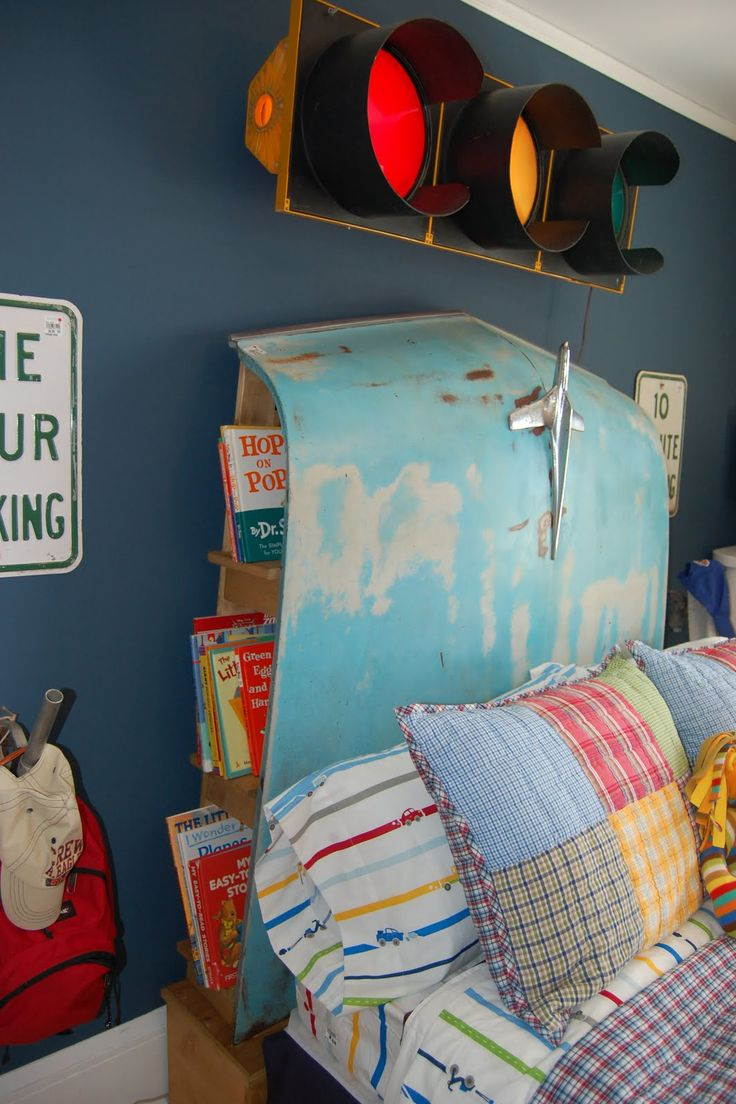 Look closely—the headboard of this bed is actually an old car hood! Built-in shelves behind the hood offer handy storage space.  Learn more at Stamp till U Cramp.   - CountryLiving.com