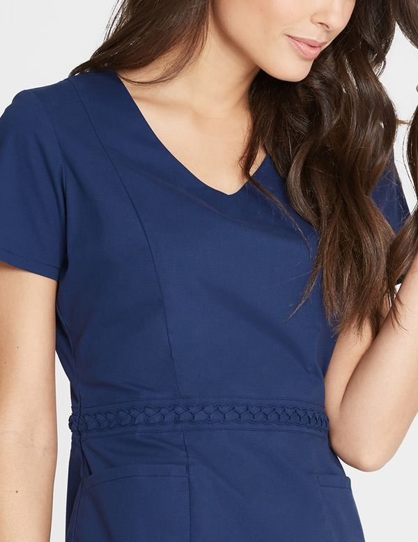 The Braided Top has intricate braided fabric trim along the waist. Also features patch pockets for easy, secured storage, a tailored silhouette with a fitted waist and our signature gold zipper on the side. #scrubs
