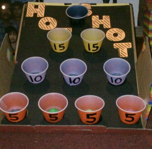 DIY Carnival-Theme Party Game made from household items! This is my homemade version of SkeeBall. #1. Paint 10 Pixie Cups and draw a point number on each row as shown. #2. Tape/Glue cups onto a poster board in this format. #3. Use an open shoe box as a base for the game. #4. Have 1-3 ping pong balls or (in my case) plastic hollow balls from an old toy gun. Voila! A fast, free, fun version of Skee Ball!