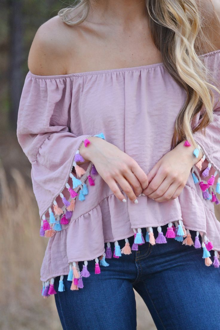 $44.00 Tassel Tango Top Off-the-shoulder AND tassels?! It doesn't get much better than this fun top! The dangling multi-colored tassels give this comfy top some serious pizzazz! The elastic band across the top allows you to wear it on or off the shoulder.