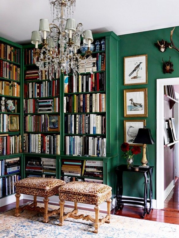 Library with green walls, leopard stools, and antique chandelier.
