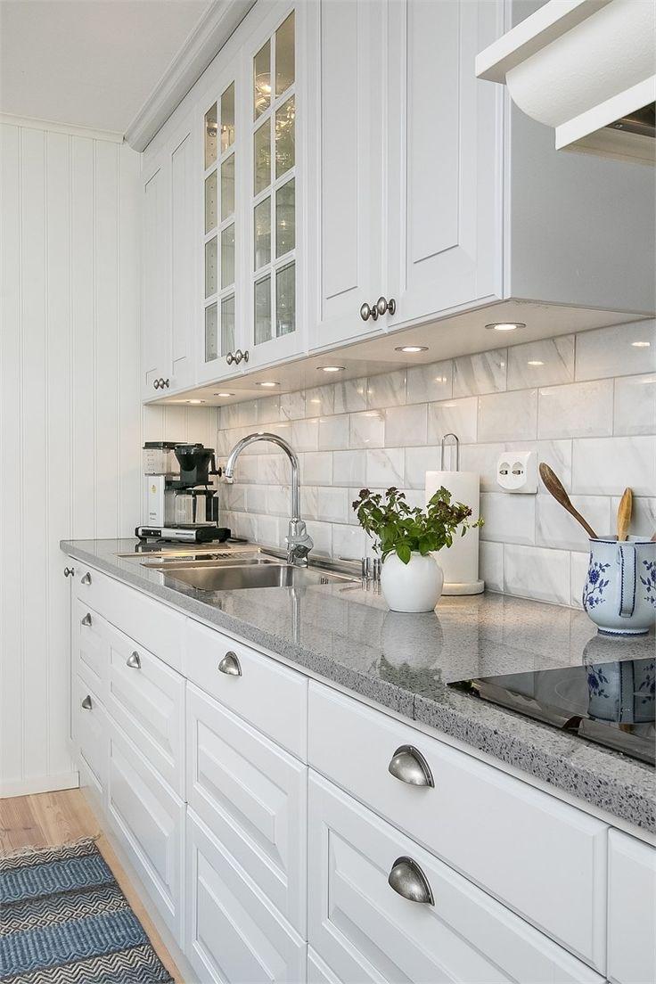 Klassiskt pärlgrått kök med vitrinskåp och en finfin stenskiva | Ballingslöv