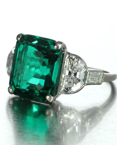 A fine art deco emerald and diamond ring, circa 1925 The cut-cornered step-cut emerald, weighing 8.41 carats, between demi-lune and baguette-cut diamond shoulders, diamonds approximately 1.85 carats total, ring size M½, modern Cartier replacement case