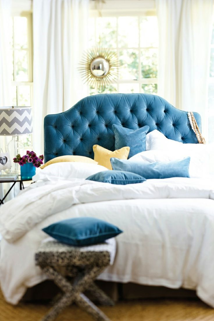Blue velvet tufted headboard with yellow accents and white linens