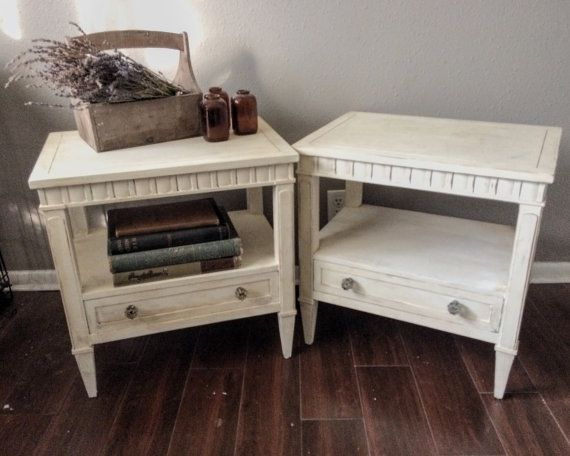 This is a pair of two farmhouse style side tables painted a warm white with antiquing finish to highlight the details. Each have an easy sliding drawer painted turquoise with two dusty grey crystal knobs. DIMENSIONS: 22.5L x 16Wx23H  The listing price of this item is for it in as is condition. Since this piece is vintage it is not in perfect condition. There may be scratches, dings and/or nicks. I do try to photograph them in order to fully disclose their previous lives. :)  For pickup in…