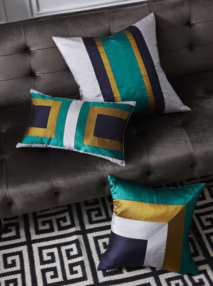 The Jonathan Adler Silk Siam Pillows are simple geometric compositions in neutral gray and navy with a glamorous pop of jewel-toned emerald. They are bold on a bedscape or subtly striking on a sofa.