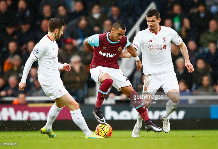Dimitri Payet (C) of West Ham United competes for the ball against Adam Lallana (L) and Dejan Lovren (R) of Liverpool during the Barclays Premier League match between West Ham United and Liverpool at Boleyn Ground on January 2, 2016 in London, England.