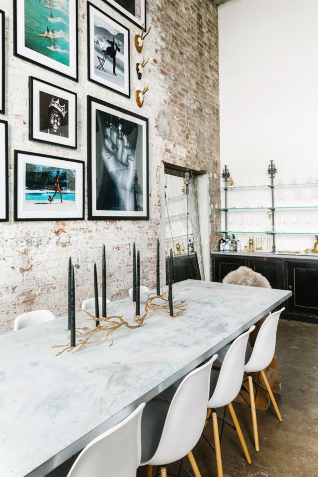 Dining space with exposed brick walls, framed art, a marble dining room table, and Eames dining room chairs (via @mydomaine)