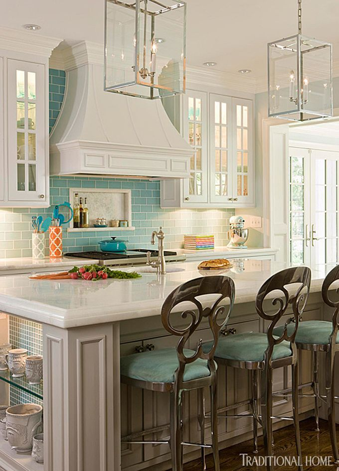 The kitchen's elegant but not overdone white cabinetry teams with pale turquoise tiles. - Traditional Home ®/ Photo: Gordon Beall / Design: Kat Liebschwager