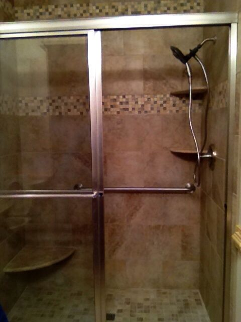 fiberglass shower replaced with tile shower equipped with safety support grab bars and sliding glass