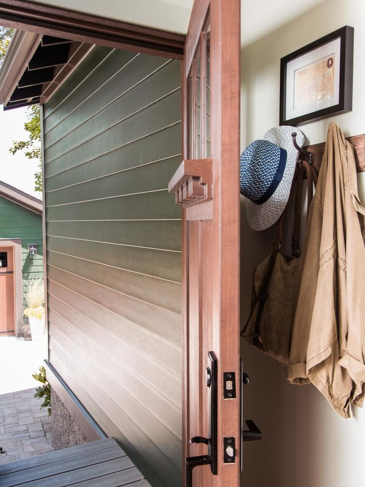 The garage is classic American, from the forest green shingled exterior to the carriage-style garage doors to the decidedly collegiate plaid papered walls.
