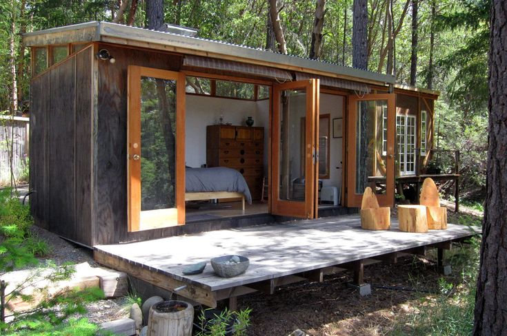 A simple modern cabin with stained plywood siding and glass doors opening to the deck. | www.facebook.com/aplaceinnature