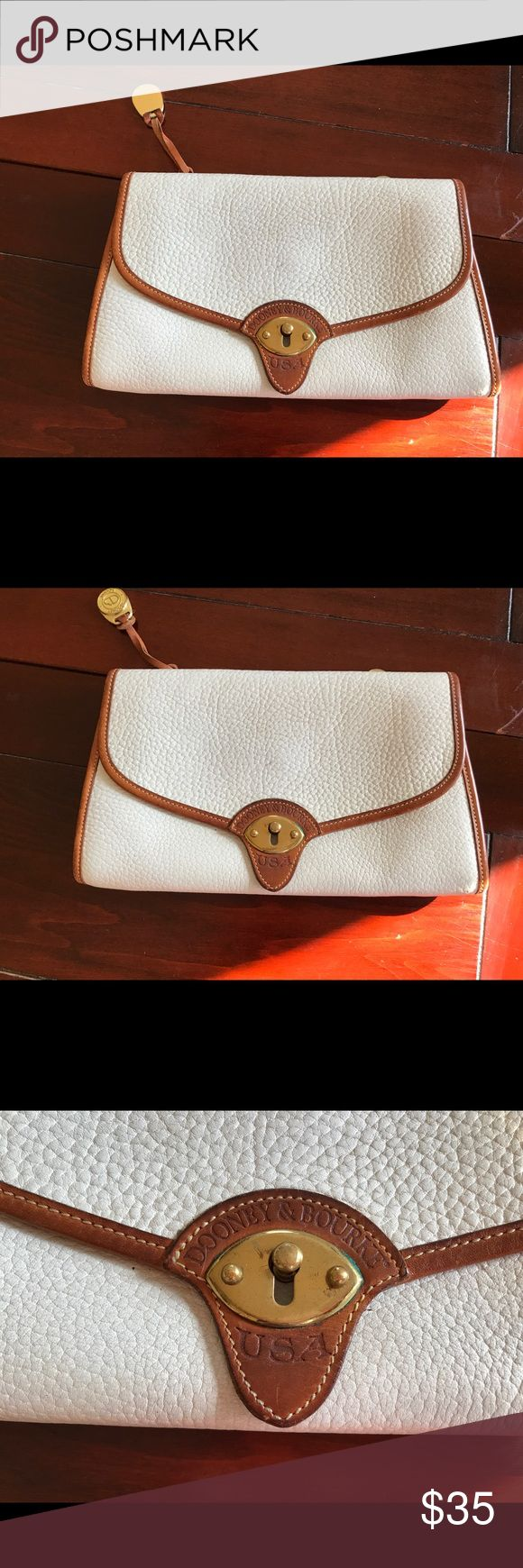 Dooney & Bourke white leather envelope clutch White pebbled leather envelope clutch with cognac trim. Can attach to a shoulder strap (not included). Lovely vintage condition. Some stray interior pen marks.  I'd love to combine this sale with an accompanying navy shoulder bag. Strap is interchangeable! Dooney & Bourke Bags Clutches & Wristlets