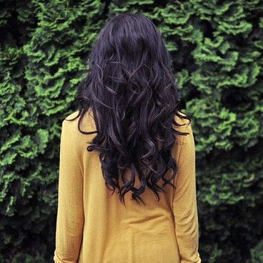 long black hair, golden shirt, and greenery.