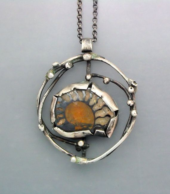 "Pendant | Temi Kucinski.  ""Fossil in a Cage 4""   Natural fossil ammonite shell slice set in sterling silver"