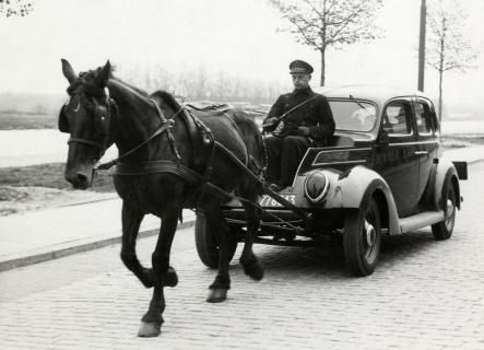 WWII. During the German occupation of The Netherlands people used a car without fuel because of shortages. In this picture a Ford V* is drawn by a horse. The spot that would usually holds the engine is now being used as the drivers' seat. Holland, The Hague, may 14th 1941