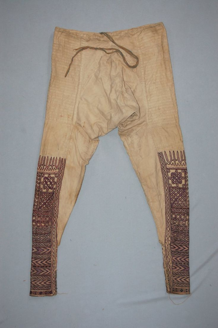 Africa, Ethiopia, man's trousers; woven of cotton, off-white cotton trousers with multi-coloured geometric designs embroidered on bottom half of each leg with silk thread; woven silk drawstring, before 1913