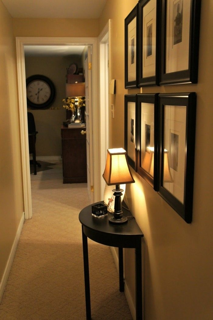 small black table, with lit table lamp, six small images in black frames, arranged in two rows, hallway furniture ideas, pale beige walls and carpet