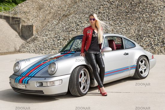 Young woman with long blond hair posing with Porsche 911 Carrera 4