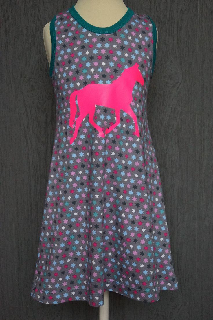 Deze eenvoudig te maken jurk is van tricot sterren multi. De halsrand en armsgaten zijn afgewerkt met boordstof petrol. De maatwerk applicatie is het paard in draf van neon roze flexfolie, 20cm groot. Een makkelijk en lekker draagbaaar zomers jurkje!