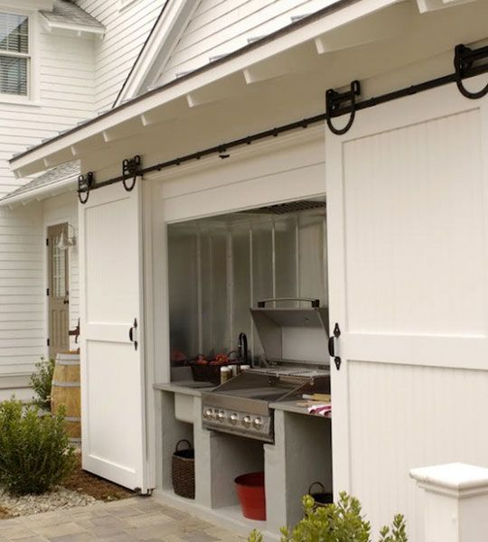 Sliding barn doors to protect your grilling area -- cool idea and prettier than your grill out in the open with a cover over it.