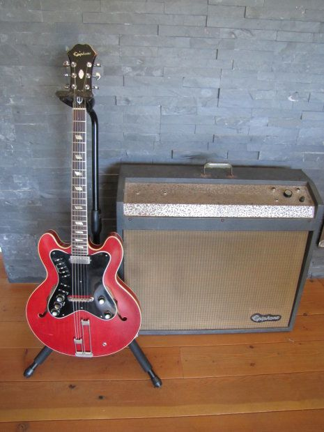 1964 Epiphone Professional Guitar / Amplifier Combo in cherry finish. The guitar is in excellent condition with replaced tuners, standard play wear for its age, some small dings on the headstock and polish swirls. The guitar comes with a newer case. All controls for the Epiphone amplifier, tremolo and reverb are mounted on the guitar. The amplifier is in excellent condition with some pitting on the chassis and features a 1956 Jensen P15N. We have also replaced the cable…