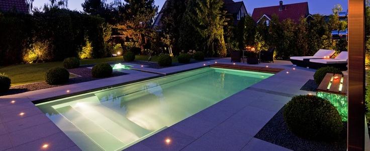 Sfeervolle tuin met modern en verlicht zwembad.