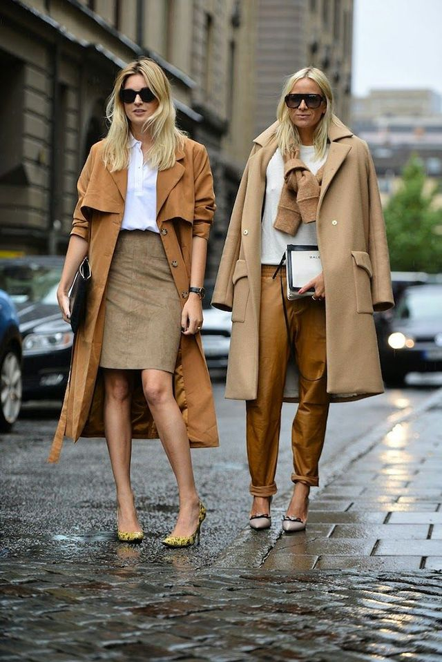 Camel coat, braun skirt whit white shirt and braun pants with white jumper. Black sunglasses.
