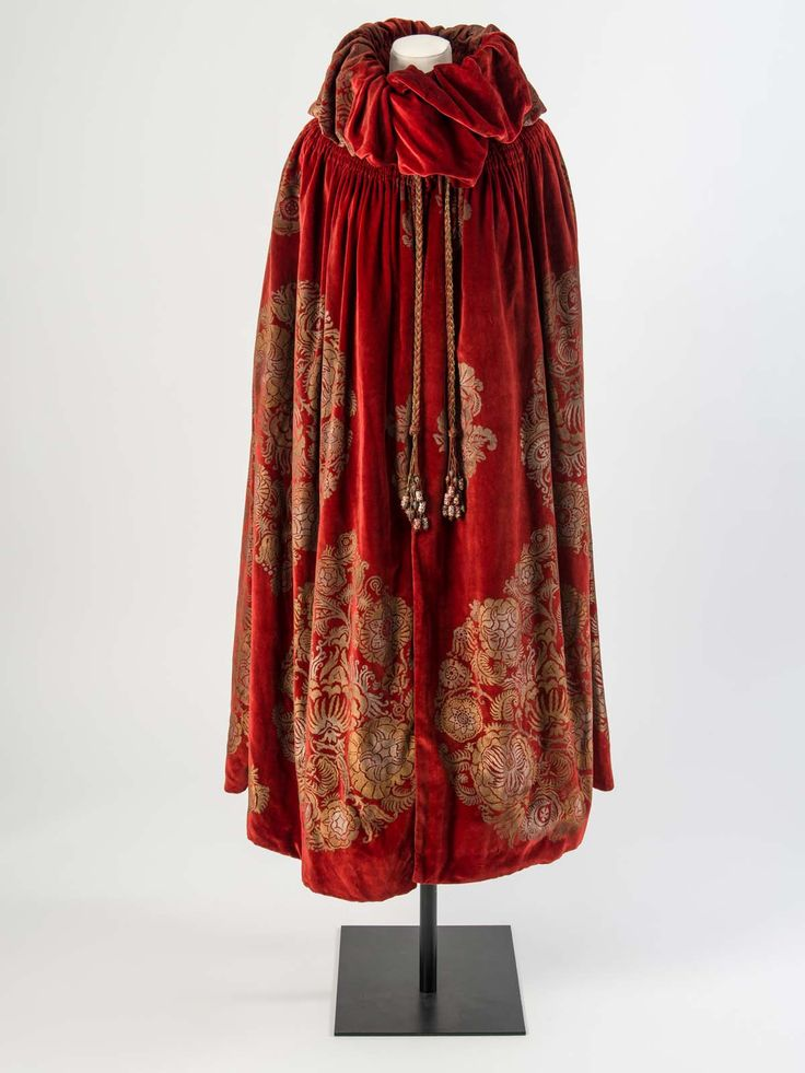 Dark red velvet cloak with a gold and silver stencilled floral design and silk tassels trimmed with painted beads, about 1923