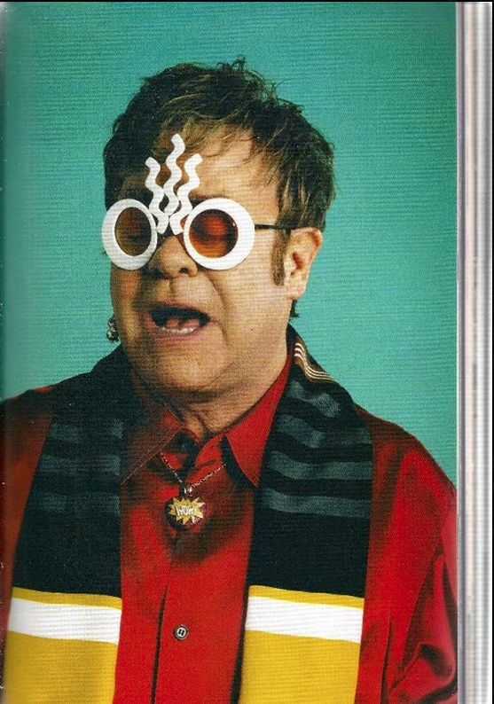 Sir Elton John wears Mercura NYC for Mercura NYC Candle in the Wind POP Art Sunglasses POP Magazine s/s/ 2011    In this photo: Sir Elton John, Vanessa Reid Fashion, Yohji Yamamoto shirt, Oliver Chanarin & Adam Broomberg Photo, The Peggy Guggenheim Issue Spring/Summer 2011, PRADA scarf, Louis Vuitton earring, Theo Fennell necklace Delphine Desane Fashion Assist, Mercura NYC for Mercura Sunglasses eyewear.