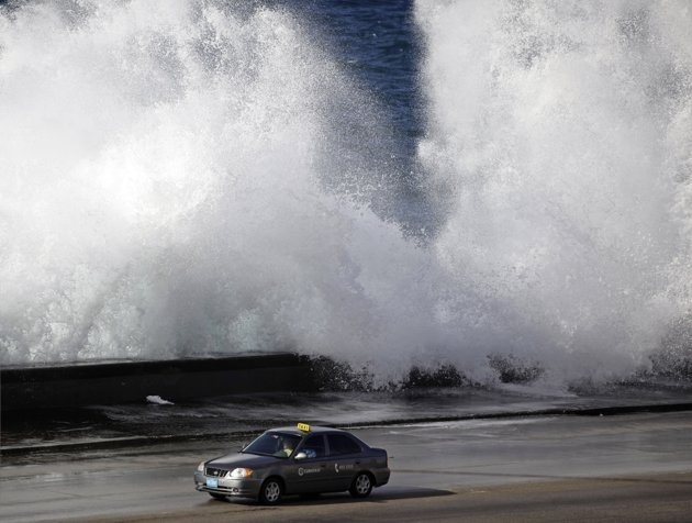 A taxi drives along Havanas seafront boulevard 'El Malecon' as waves break Mar 13, 2010. (Reuters/Desmond Boylan) Cuba - Tags: Society Environment Images of the Day