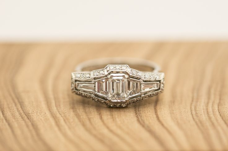 Handmade platinum diamond engagement ring. Art Deco Design. Emerald cut diamond, flanked by two baguette cut diamonds. 2pt diamonds surround the centre setting. Design features include millgrain edge, halo around centre setting and detailed shoulders and under-basket. Handmade using traditional tools and techniques by Terry Cockrem. #Custom #Design #Luxury #Engagement #Bridal #Wedding #Jewellery #MasterJeweller #TerryCockrem #RoseandCrownJewellers #Platinum #Gold #Diamond #Sapphire #Emerald