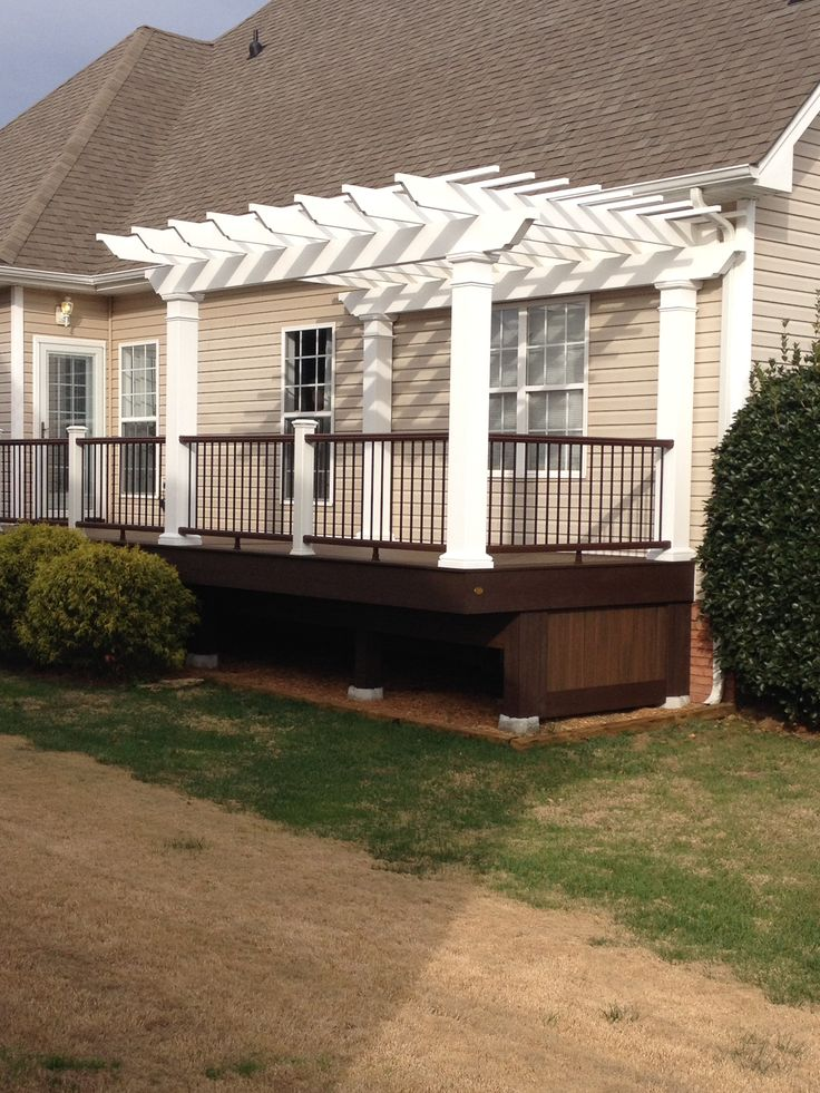 A portion of this classic Trex deck is enclosed by a freestanding and attached classic Trex Pergola kit. The pergola is a freestanding kit, but the rafters have been attached to a wall mounted ledger for additional stability. The fiberglass columns have been integrated into the deck railing to maximize the usefulness of the deck.