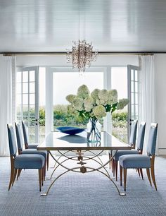 Blue, gold and white dining room set for 6 people with pale blue, upholstered dining chairs and a rectangular glass dining table in the project of Elissa Cullman