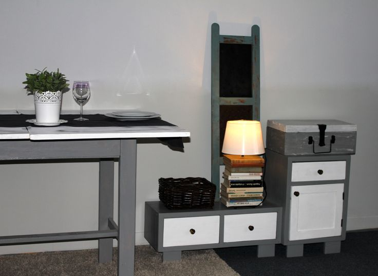 A cute gray-white table with a matching small cabinet.