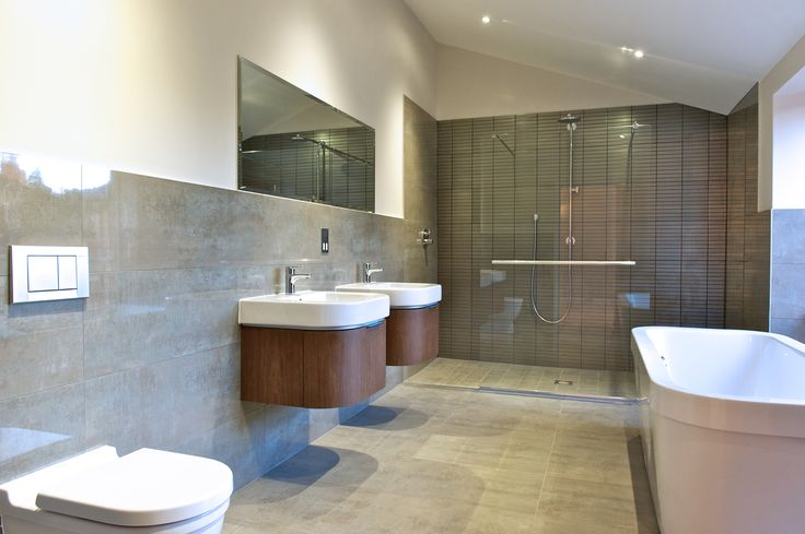 Spacious bathroom featuring a walk through shower, double washbasins, wall hung toilet and bath. Copyright The Designer Knowledge.