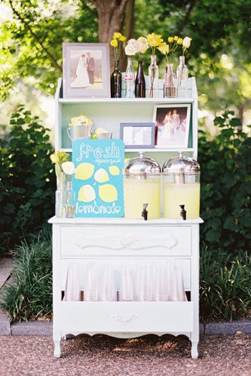lemonade stand - love the old dresser for display. Notice the old bottles with flowers and old wedding photos (parents of the bride and groom? ... could also do engagement pics)