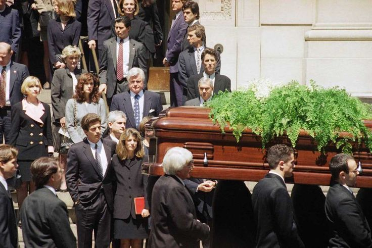 The casket bearing the remains of Jacqueline Kennedy Onassis is carried out of St. Ignatius Loyola Roman Catholic Church in New York following a funeral mass  Monday, May 23, 1994. Following immediately behind the pallbearers are John F. Kennedy Jr., with an arm around his sister, Caroline Kennedy Schlossberg; Carolineís husband, Edwin Schlossberg, is visible between them. Hillary Rodham Clinton, left; Sen. Edward M. Kennedy (D-Mass.) and his wife, Victoria Reggie, center; and at right…