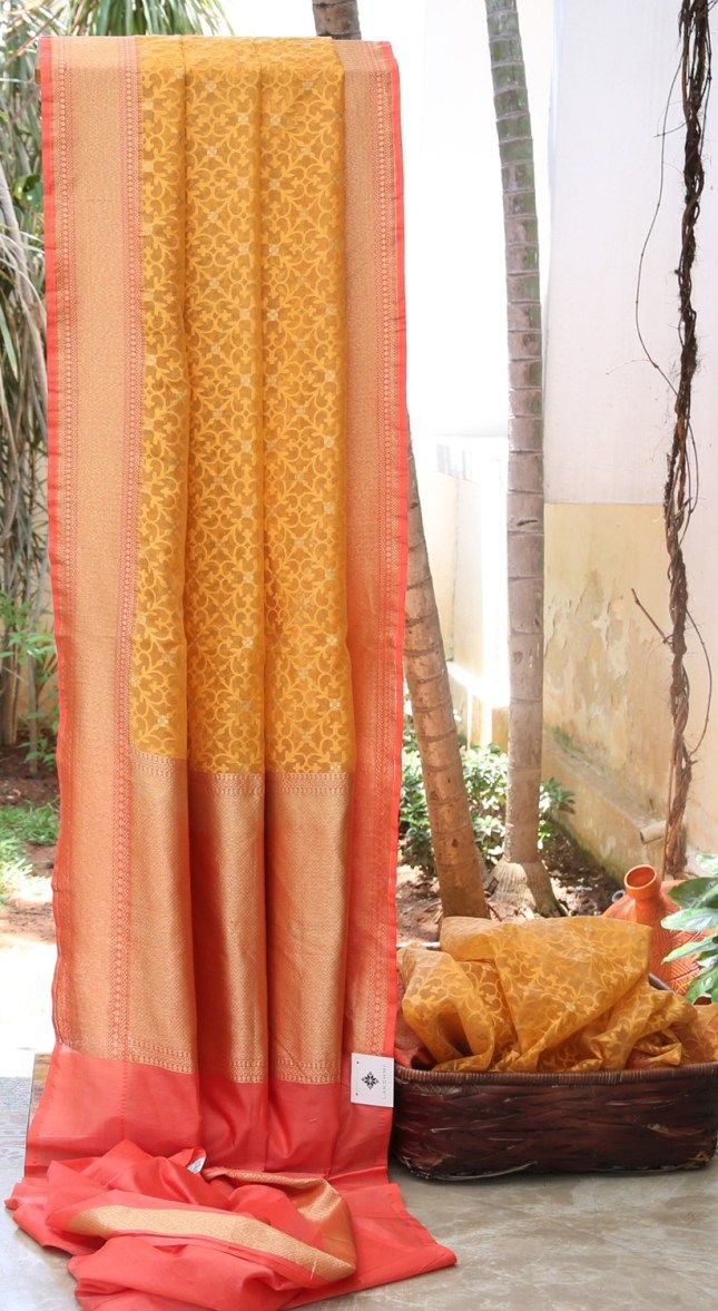 ALLURING LIGHT ORANGE BENARES KORA WITH A SIMPLE TEXTURED ORANGE ALL OVER. THE PEACH WITH GOLD ZARI BORDER AND PALLU HIGHLIGHTS THE ELEGANCE OF THE SAREE.