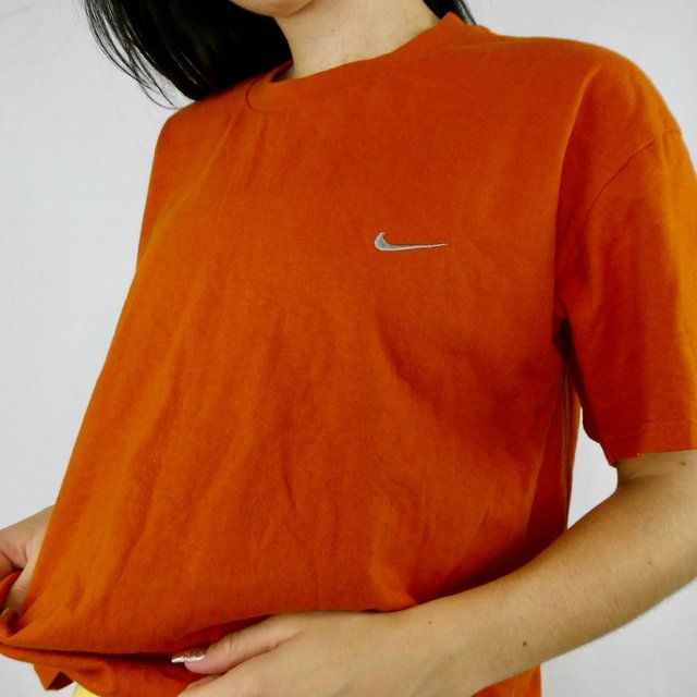 RETRO ORANGE NIKE GRAPHIC SIZE M/L!    MESSAGE FOR BUNDLE DEALS  26$ CAD/19$ USD   shipping is worldwide.  8.99 to Canada  16.99 for non tracked surface shipping which will be 2 weeks to 2 months depending on where you live for international. shipping to U.S takes A a week or two!  18$ to US for tracked and takes 5 days. - ask for price change! 18$ cad/13$ usd   Tags Harley Davidson Y2K Tommy Hilfiger graphic polo Ralph Lauren NAUTICA kappa Hugo boss