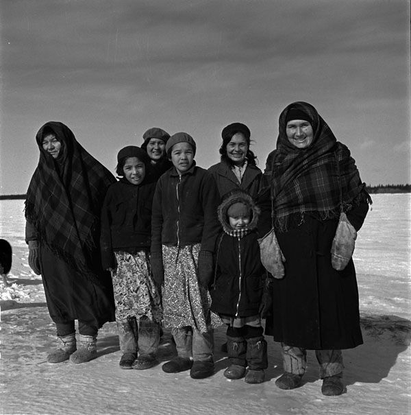 Group of Cree women and children standing in the snow and smiling at the photographer, Chisasibi, Quebec  (item 1)