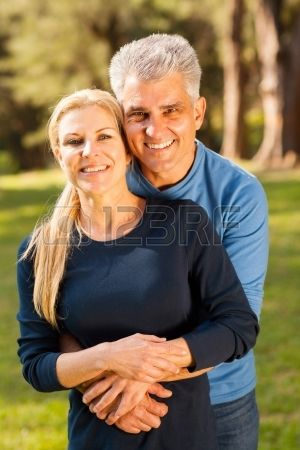 happy middle aged couple hugging outdoors